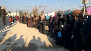 Filas de pessoas na cidade de Moadamiyeh, Síria durante uma distribuição de ajuda alimentar conjunta entre o equivalente da Cruz Vermelha, o Croissant Rouge Árabe Sírio (SARC) e o Comité Internacional da Cruz Vermelha, que ocorreu em uma zona tampão.