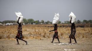 Des femmes transportent des sacs de nourriture distribués le 4 mars 2017 à Ganyiel, au Soudan du Sud.