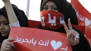 "An anti-government protester with a banner reading, ""I Love Bahrain"" in a rally organized by the main opposition"