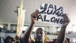 Un membre de la Ligue des jeunes de l'ANC arborant une pancarte «Laissez Zuma tranquille», le 9 avril 2017 à Durban.