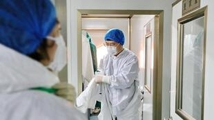 A laboratory worker puts on protective suit before examining specimens at a centre for disease control and prevention following an outbreak of the novel coronavirus in the country, in Qinhuangdao, Hebei province, China February 11, 2020.
