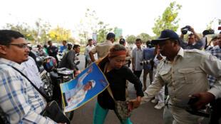 Un policier cambodgien s'en prend à une manifestante venue soutenir l'opposant Kem Sokha devant la Coup d'appel de Phnom Penh.