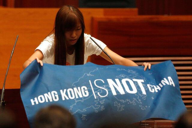 """香港本土派政党""""青年新政""""议员在宣誓就职仪式上展示写有""""香港不是中国""""字样的旗帜,2016年10月12号"""