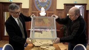 Election officials empty a ballot box to count votes from the first-round local elections, 22 March 2015.