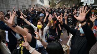 Les manifestants dont certains tenaient des parapluies jaunes, un symbole du mouvement prodémocratie, scandaient « Libérez les prisonniers politiques ! », « Debout pour Hongkong ! »