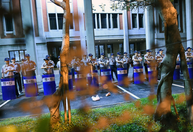 Cảnh sát canh gác bên ngoài Bộ Giáo dục ở Đài Bắc khi sinh viên biểu tình ngày 30/07/2015.