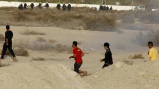 Opositores al rey huyen intentando escapar del gas lacrimógeno disparado por la policía anti disturbios.