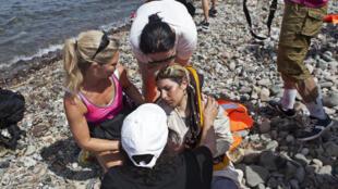 Des volontaires aident une réfugiée syrienne échouée sur les iles grecques de Lesbos, le 7 septembre 2015.