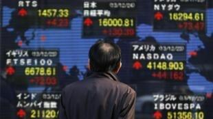 Un peatón observa una pizarra electrónica con índices económicos internacionales, Tokio, 24 de diciembre de 2013.