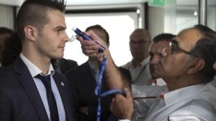 Доктор аэропорта Шарль де Голль демонстрирует на сотруднике полиции как будут измерять температуру авиапассажирам из западной Африки, 17 октября 2014 г.