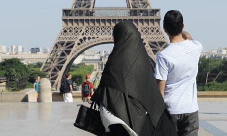 Женщина в никабе перед Эйфелевой башней в Париже