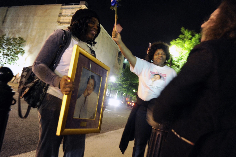Fuera de la Casa Blanca, un par de mujeres muestran la foto de su tía asesinada en los ataques al Pentágono el 11 de septiembre del 2001