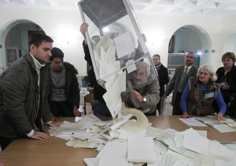 Des responsables locaux duprrocessus électoral vident les urnes après la fermeture de leur bureau de vote, à Kiev, le 28 octobre 2012.