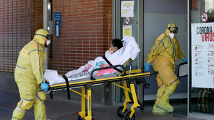 کادر درمانی در حال انتقال یک فرد مبتلا به ویروس کووید ۱۹ به بیمارستانی در اسپانیا هستند.