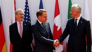 O ministro da Economia e das Finanças, Bruno Le Maire (à direita), cumprimenta o presidente do Banco da Alemanha, Jens Weidmann, ao lado do presidente do Banco da França, Francois Villeroy de Galhau, em Chantilly.