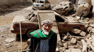 Un homme se tient près de voitures endommagées par une frappe aérienne dans la ville d'Amran, au Yémen, le 25 juin 2018.