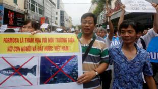 Le dissident Nguyen Xuan Dien (c) tient un panneau sur lequel est écrt: «Formosa est un désastre pour l'environnement maritime du Vietnam, pour le pays et pour sa population». Hanoï, le 1er mai 2016.