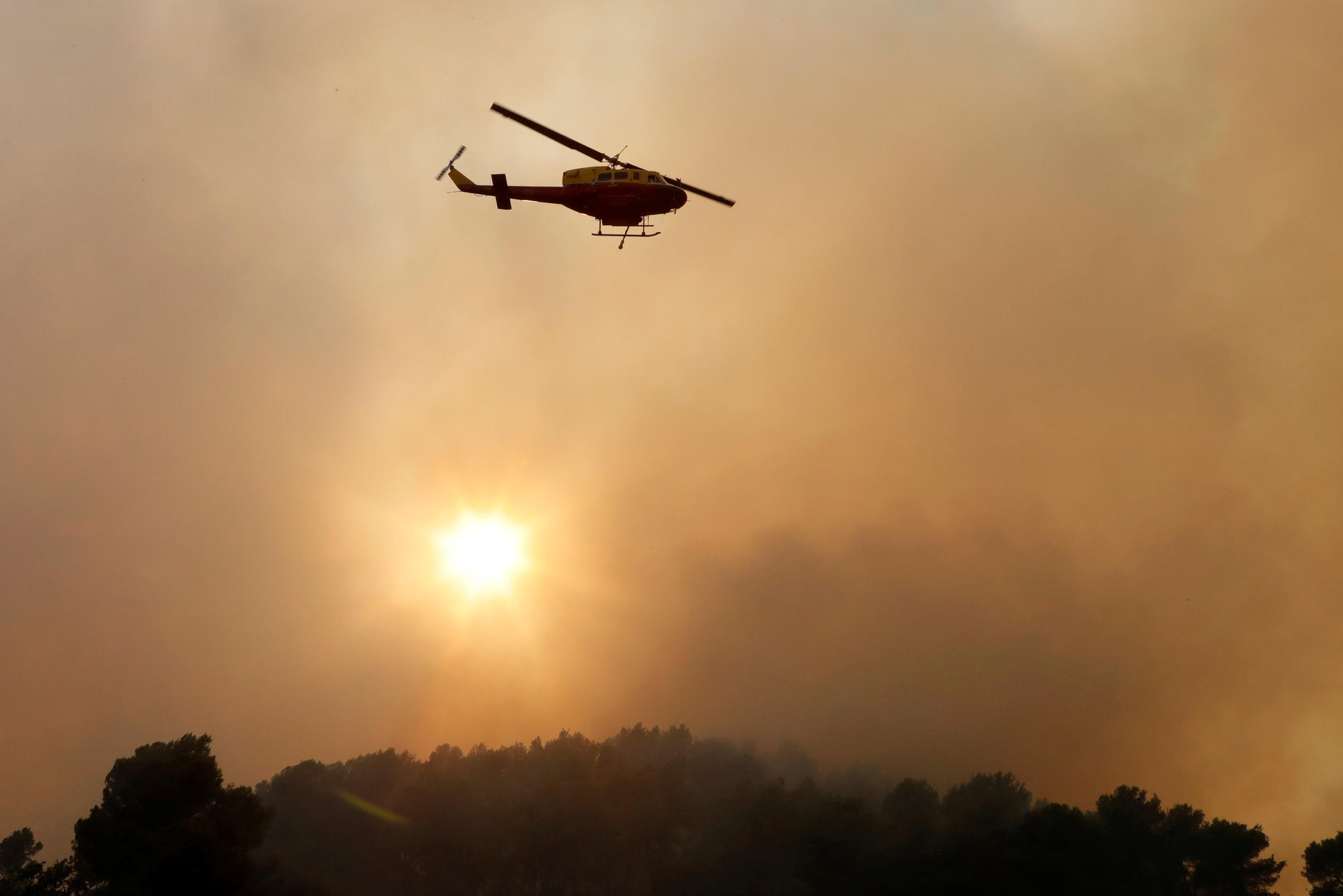 A helicopter flies over a fire at Carros, near Nice