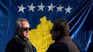 Deux hommes discutent devant le drapeau du Kosovo.