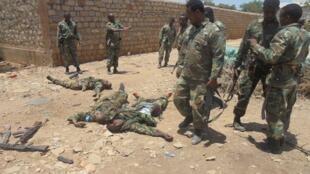 索马里士兵和非盟维和军人在伊斯兰青年党袭击者尸体旁2015年3月12日拜多阿