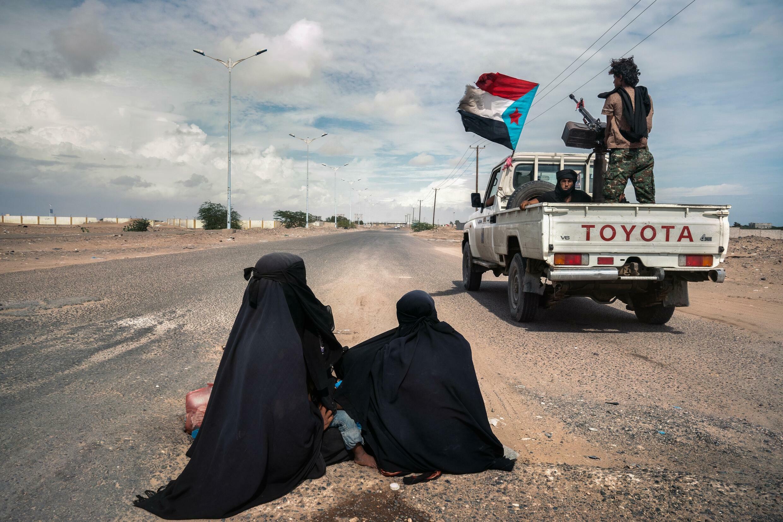 Aden, Yémen. Décembre 2020. Des soldats du Conseil de transition du Sud (STC) passent à toute vitesse devant deux femmes mendiantes Muhamasheen à Lahj, au Yémen. La caste des Muhamasheen a longtemps été considérée comme le peuple le plus marginalisé du Yémen et traitée comme un paria social. © Giles Clark