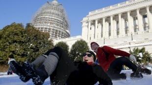 Pessoas brincam de deslizar na neve em frente do Capitólio, Washington 24/01/16