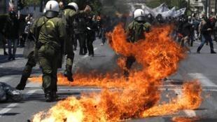 Una bomba de petróleo explota cerca de un militar durante las manifestaciones de este 11 de mayo en Atenas