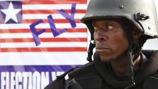 A riot police officer stands guard near a banner of a Liberian flag in front of the National Elections Commission building.