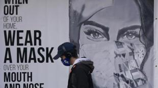 """Homem passa diante de um cartaz em São Francisco, Estados Unidos, onde está escrito """"use máscara""""."""