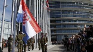 Soldados del Eurocuerpo alzan la bandera de Croacia frente al Parlamento Europeo en Estrasburgo, este 1 de julio de 2013.