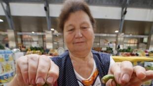 Une vendeuse de légumes brandit fièrement des poivrons venus de Crimée, sur un marché de Saint-Petersbourg, ce jeudi 7 août.