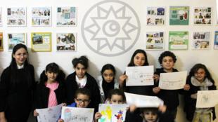 Les enfants montrent leur dessin, lors de l'atelier Bande-dessinée proposé par la scénariste Amir Gasmi.