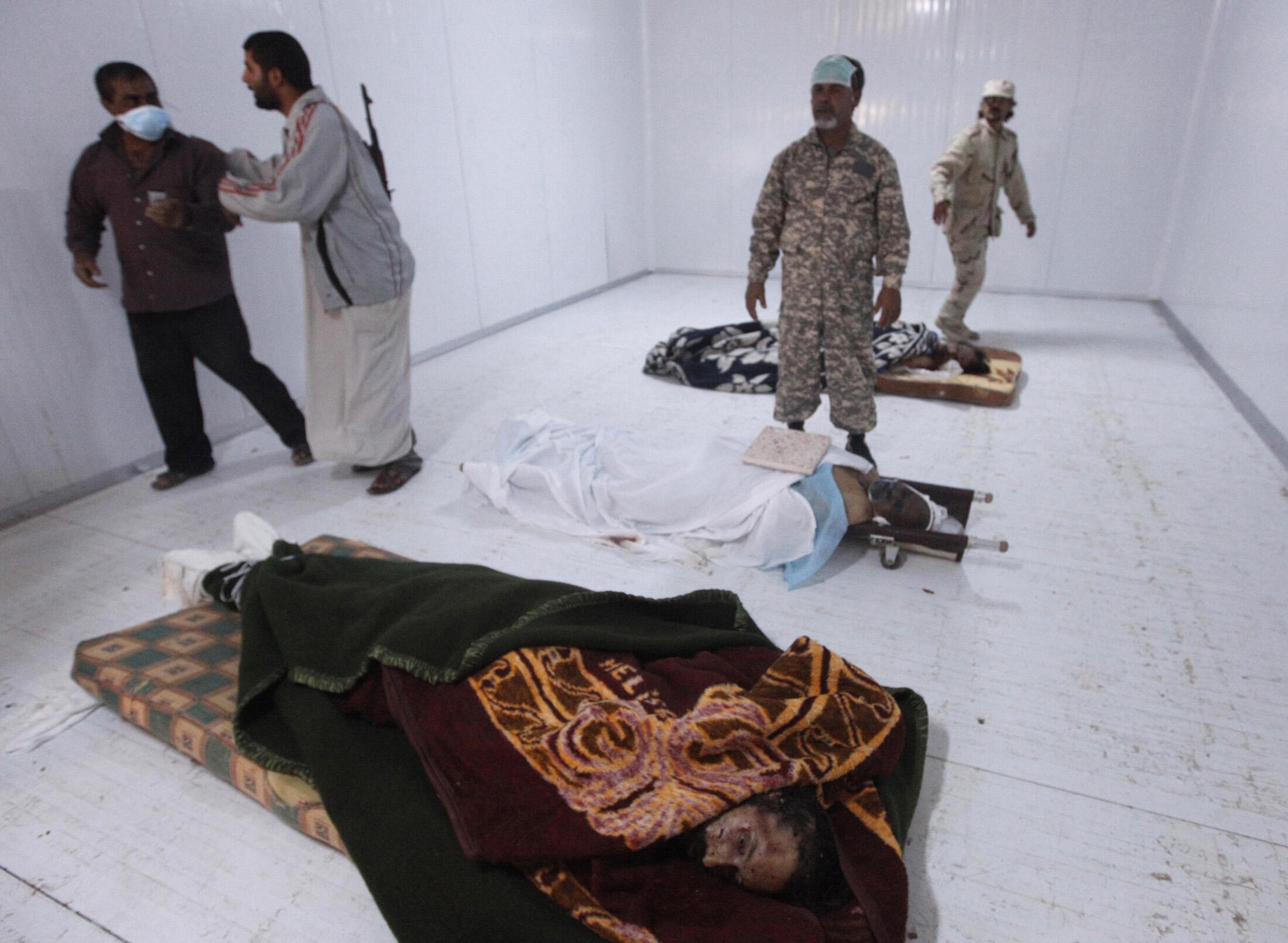 Тела Муаммара Каддафи, его сына Муатасима (внизу) и их телохранителя Абу Бакр Юниса (в центре) в металлическом холодильном контейнере в Мисурате 22 октября 2011 года