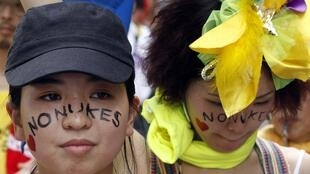 Protesters bearing anti-nuclear face-painting take part in an anti-nuclear march in Hiroshima 6 August 2011.