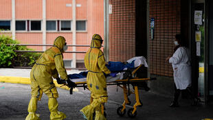 Healthcare workers bring a coronavirus patient to hospital in Leganes, near Madrid, 11 April 2020. The death toll from the disease rose Sunday, after dropping for three straight days.
