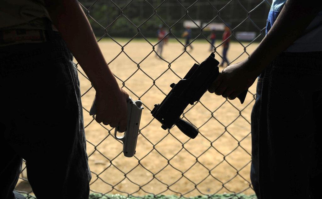 Le vol d'armes à feu, un vrai danger pour les policiers au Venezuela. Deux enfants armés, près d'un terrain de jeu.