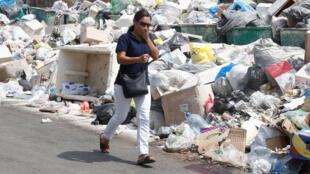 Une femme se couvre le nez pour traverser une rue jonchée de détritus, le 29 août 2016 à Dkwaneh.