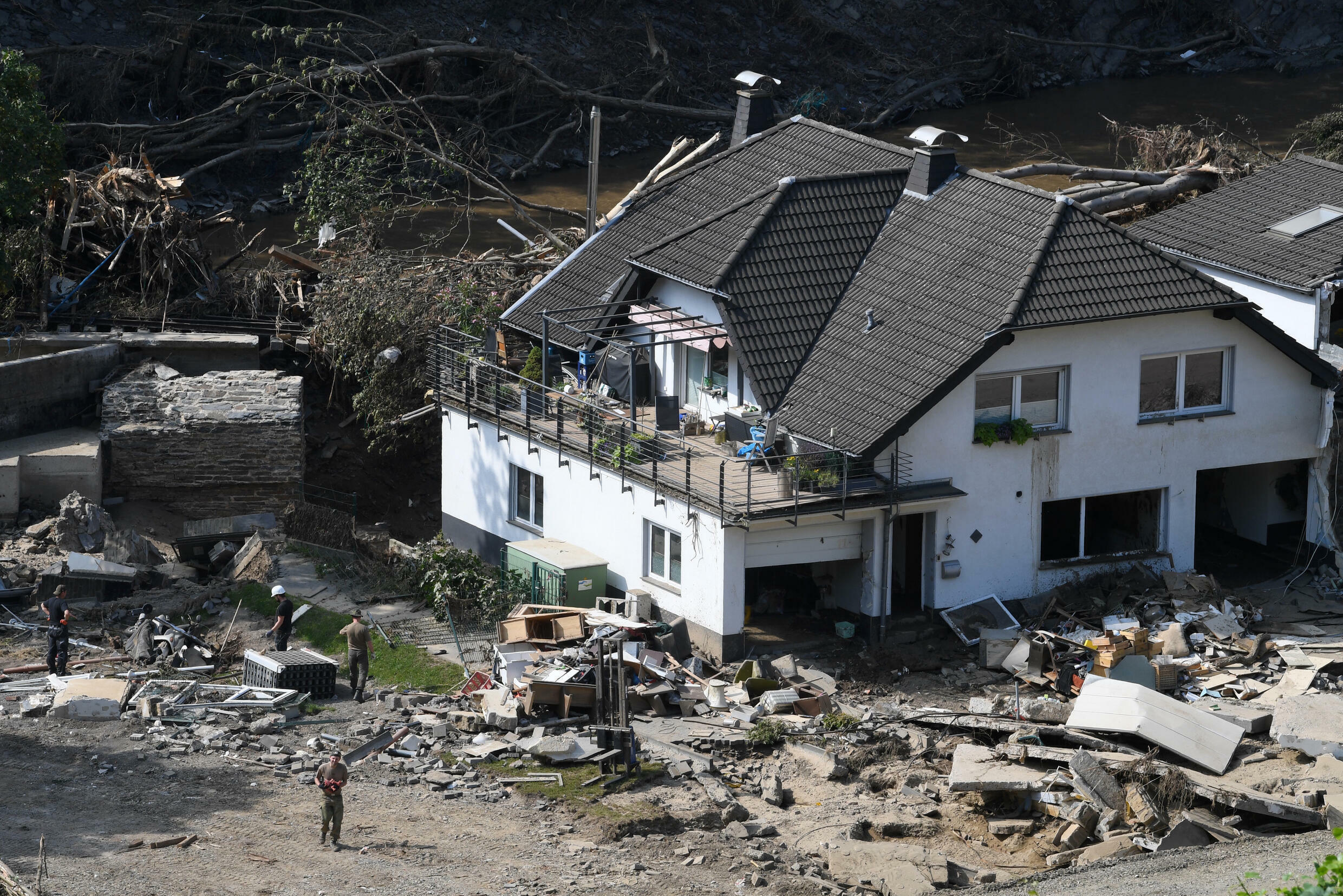 Workers on Thursday clear around a damaged home in Marienthal, in the Bad Neuenahr-Ahrweiler distict of western Germany, more than week after deadly floods struck the region