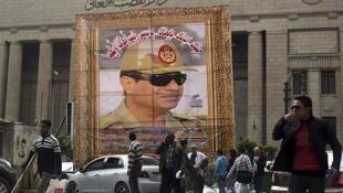 Personas caminan frente a la Corte Suprema de Egipto y un cartel con el nuevo hombre fuerte del país, Abdel Fatah al Sisi, el 13 de marzo de 2014.