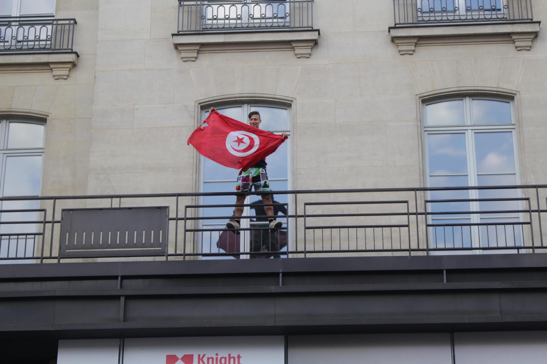 Rapaz mostra bandeira da Tunísia