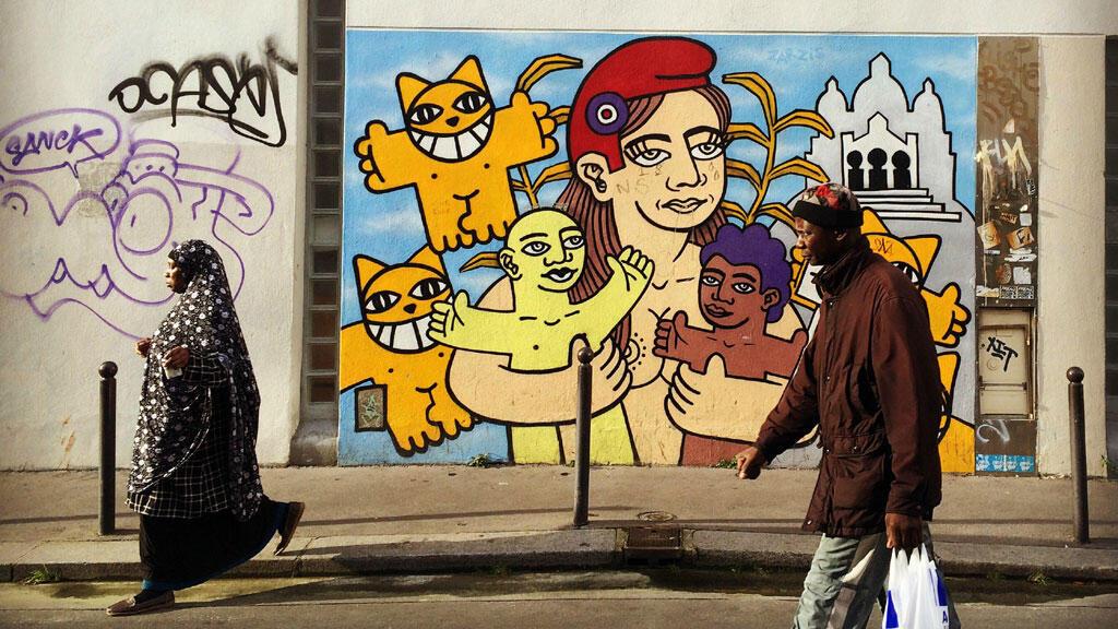 Dans la rue Polonceau à Barbès avec, en fond, une œuvre du graffeur M. Chat.