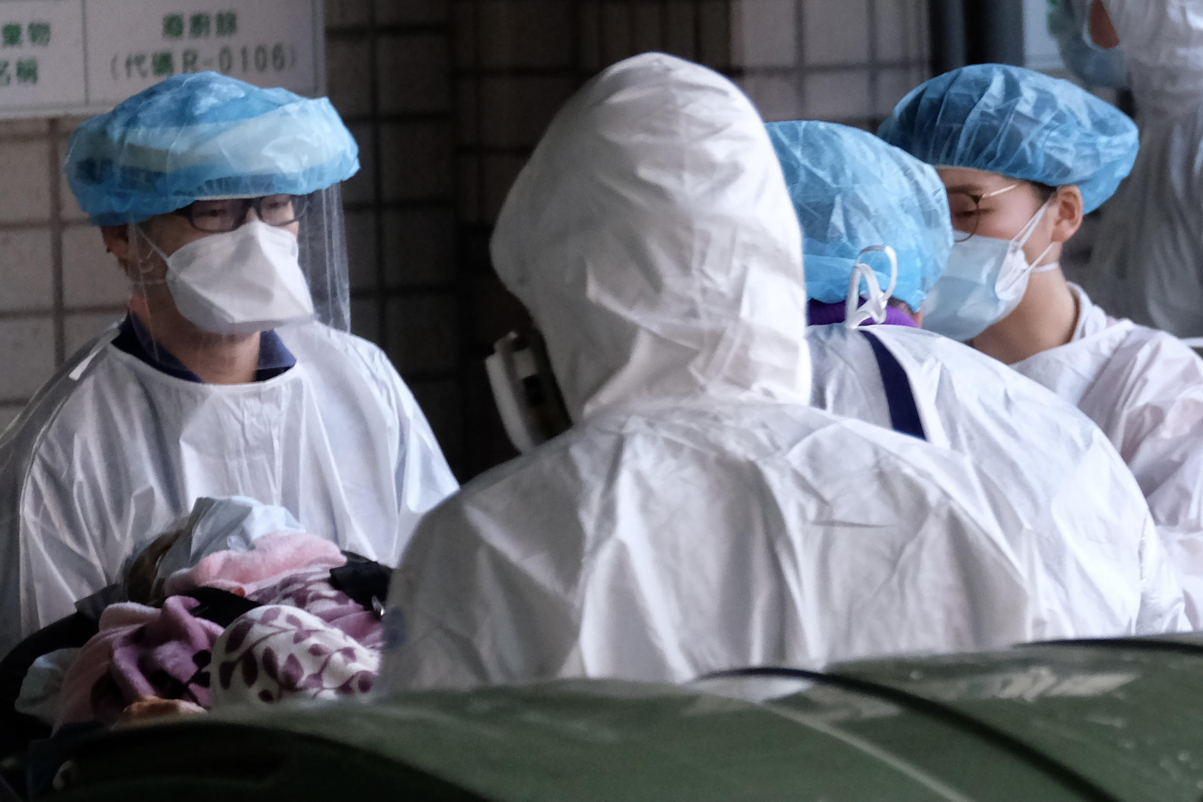Masked medical staff escort a patient in January 2021 outside the Taoyuan General Hospital as Taiwan contained a small cluster of Covid-19 cases