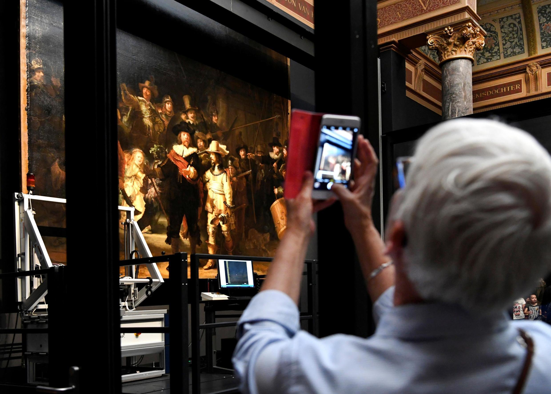 Une femme prend une photo de la célèbre « Ronde de nuit » de Rembrandt au Rijksmuseum d'Amsterdam.