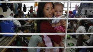 Une jeune fille dans ses bras, sa petite soeur, a trouvé refuge dans une école à Manille le 8 août 2012.