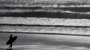 Surfista na praia de Montalivet-les-Bains, no oeste da França, no sábado (14).