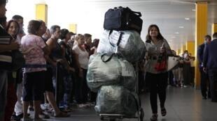 Một hành khách với hành lý cồng kềnh từ Miami đến sân bay quốc tế ở La Habana ngày 30/08/2014. Chính quyền đã nâng thuế đánh vào hàng tiêu dùng để hạn chế thị trường chợ đen.