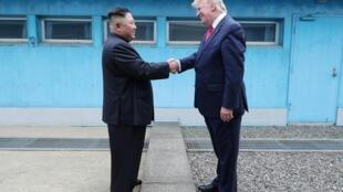 Le président américain Donald Trump (d.) serre la main du dirigeant nord-coréen Kim Jong-un lors de leur rencontre dans la zone démilitarisée séparant les deux Corées, à Panmunjom, Corée du Sud, le 30 juin 2019.