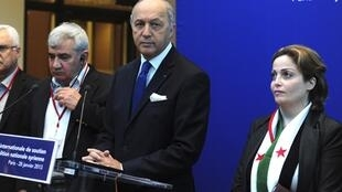 French Foreign Minister Laurent Fabius (C) with Riad Seif (L) and member Suheir Atassi (R) in Paris