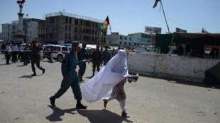 Una mujer pasa junto a un miembros de las fuerzas de seguridad cerca del lugar de un atentado suicida en el bazar de Mandawi, en la ciudad de Mazar-i-Sharif, el 9 de agosto de 2016 al norte de Afganistán