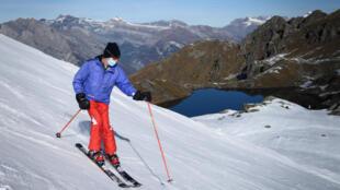 Un esquiador con mascarilla en una pista de esquí en Verbier en los Alpes suizos el 15 de noviembre de 2020